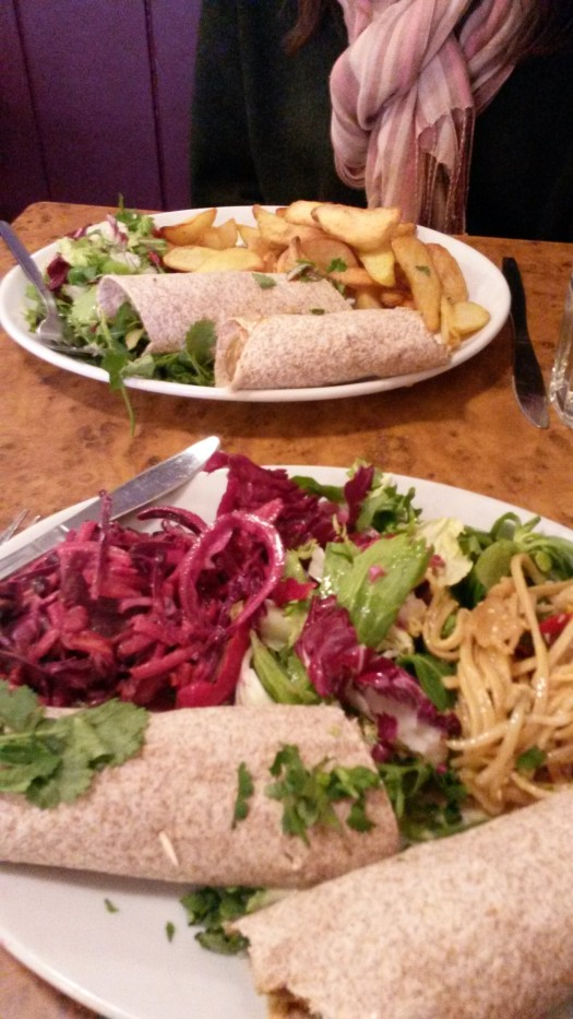 Image shows two plates with falafel wraps, salad and chips.