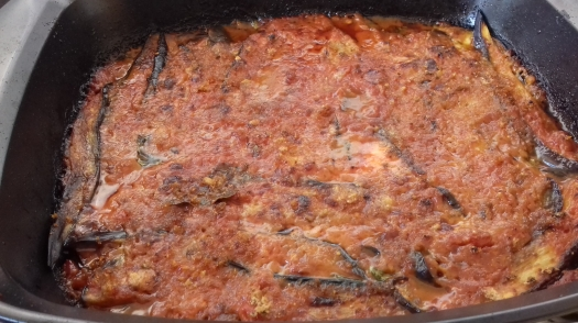 Image shows a square black baking tray containing cooked melanzane parmagiana, sliced aubergines in a red tomato sauce toped with melted cheese
