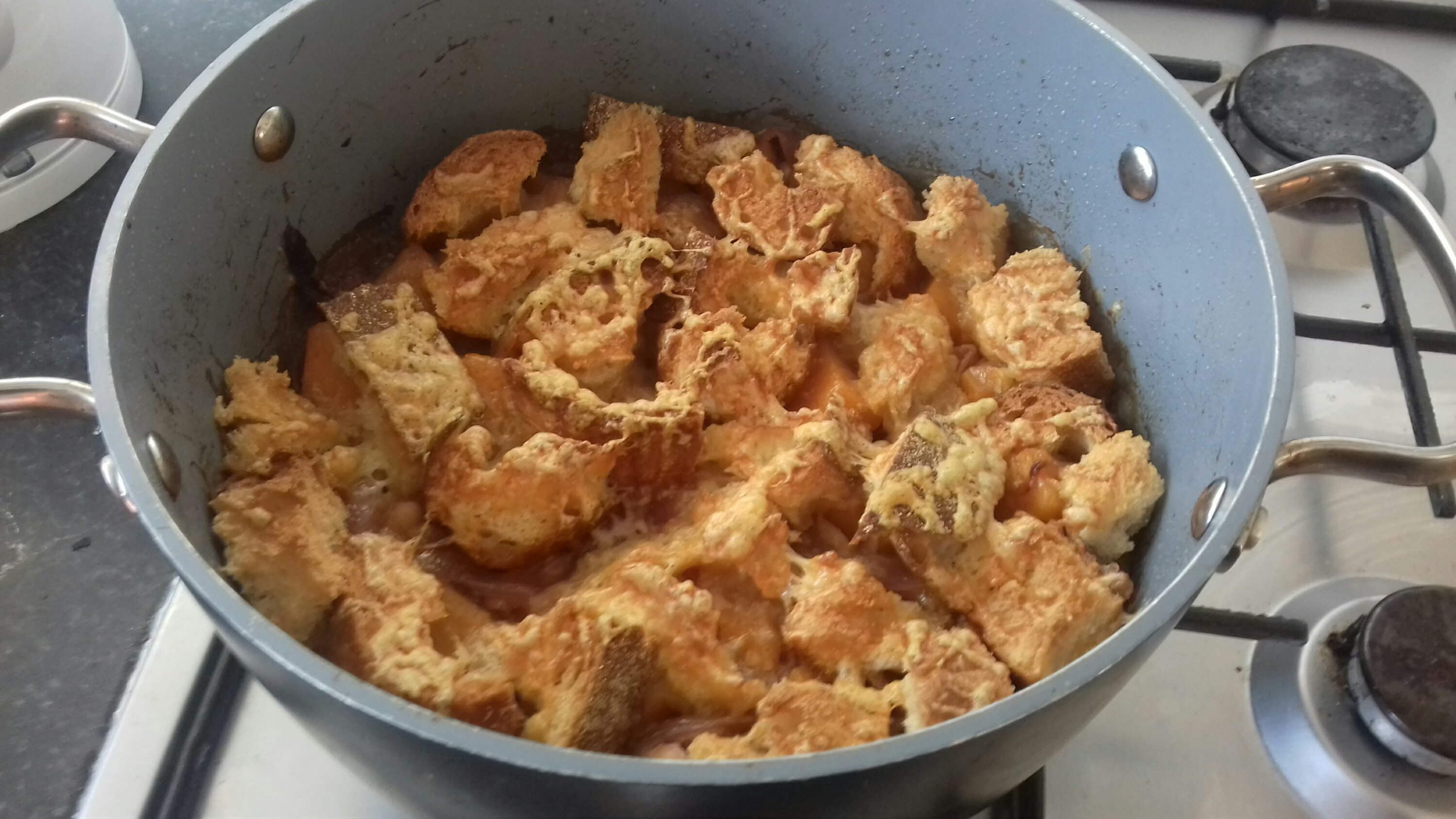Image shows a cooked gratin in a round, black oven dish. The top is covered in chunky toasted bread and grated cheese.