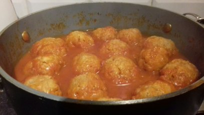 Image shows a round black casserole containing a red stew covered with dumplings on top