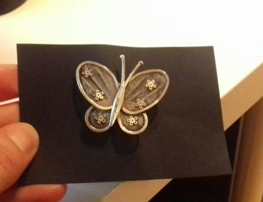 Photograph of a silver metal butterfly broach on black paper.  It is made in a naive style and looks at bit like it was drawn by a child.