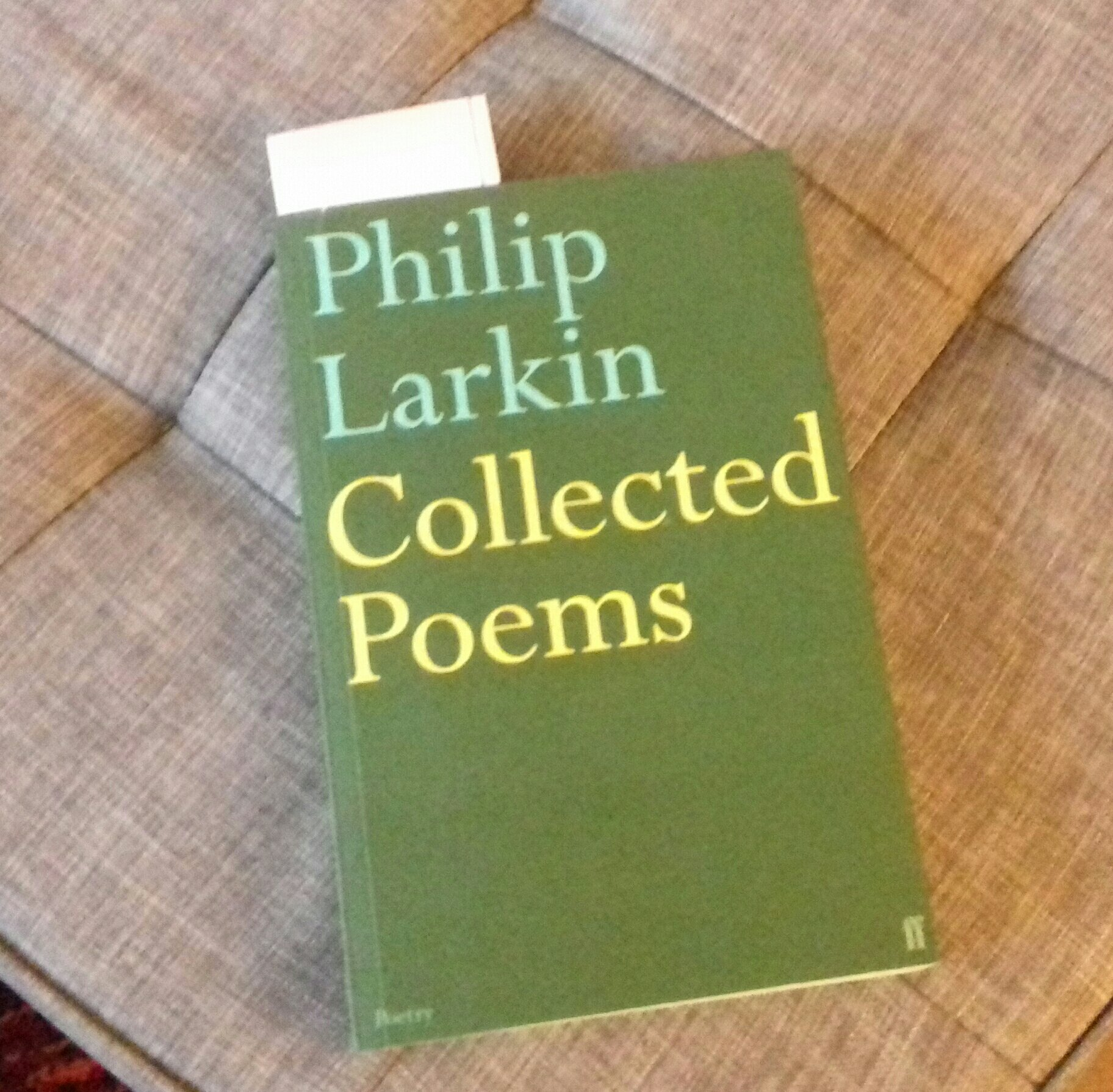 Photograph of the Faber edition of Philip Larkin's Collected Poems. The book has a plain sage green cover with the poet's name and the title.