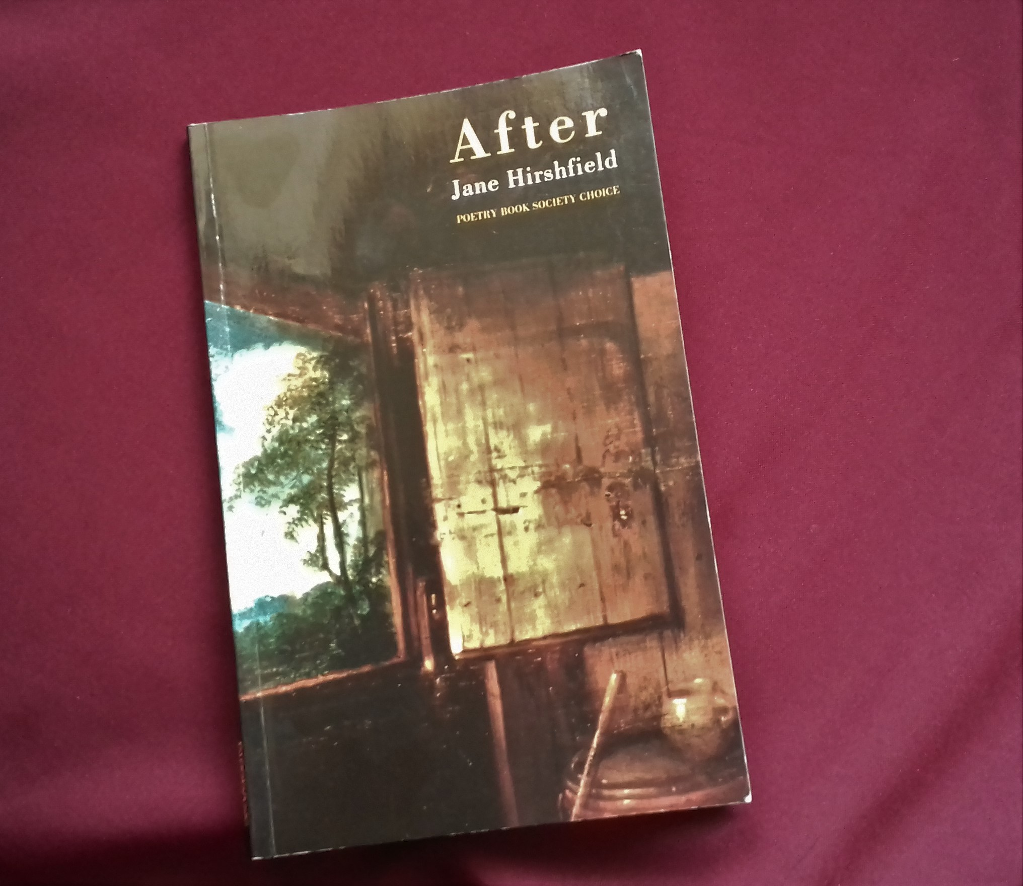 A photograph of the collection 'After'. The cover of the book is a painting of a window opening onto a landscape with trees and sky.