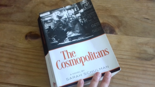 A copy of The Cosmopolitans resting on a brown wood table. The cover features a black and white photograph of a diner from the 1950s.