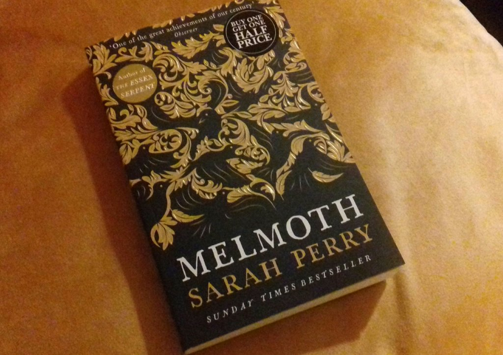 Photograph of Sarah Perry's novel Melmoth. The cover is black with a gold embossed design featuring stylised leaves.