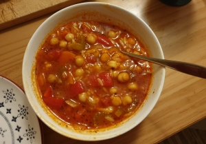 A round white bowl full of a red tomatoey soul with red peppers and chickpeas