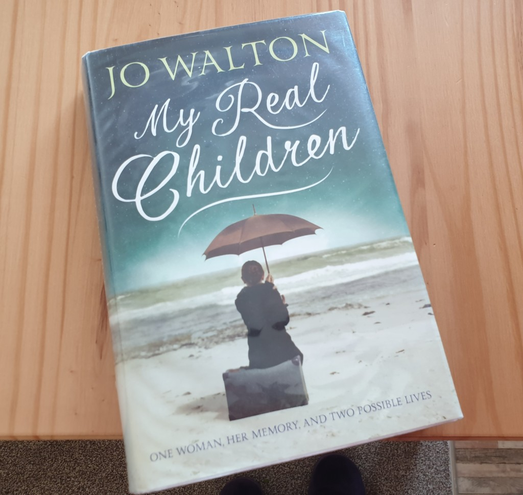 A hardback copy of My Real Children by Jo Walton. The cover shows a woman sitting on a beach and looking out to sea holding an umbrella over her head.