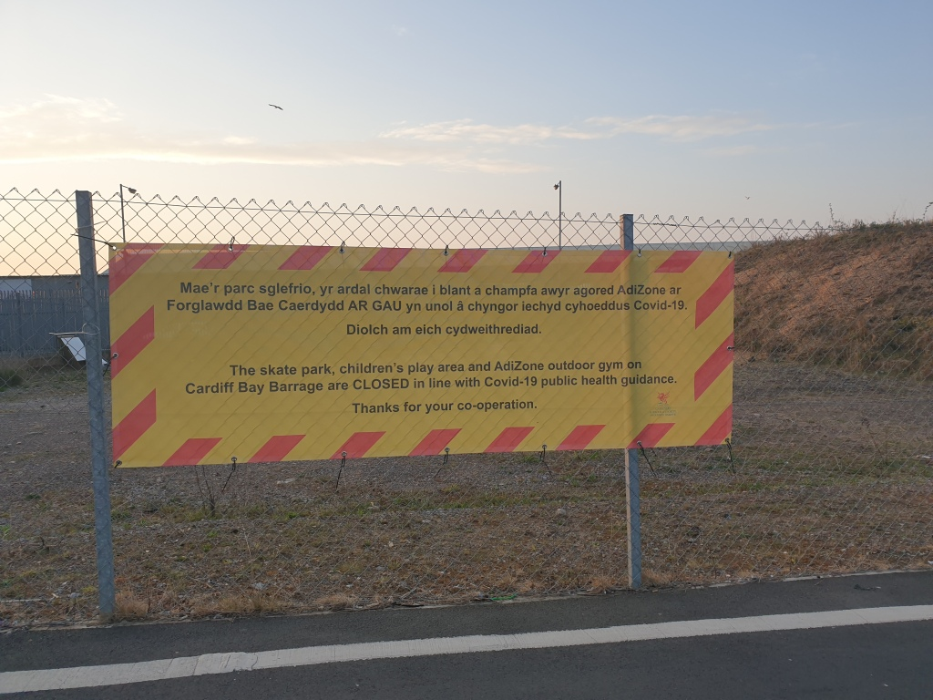 A yellow sign with red stripey border warning people that the children's play area and outdoor gym on the Cardiff Bay Barrrage are closed and not to be used.