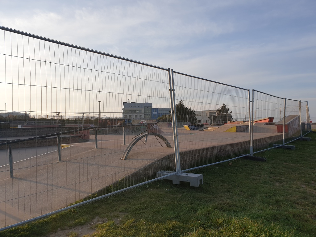 An empty skate park surrounded by metal fences