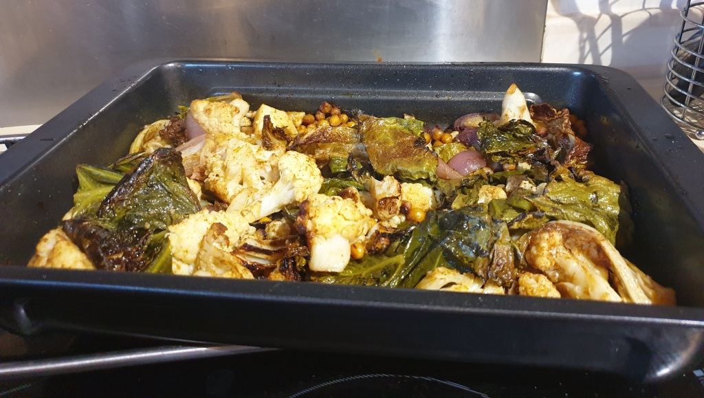A rectangluar roasting tray containing roast cauliflower, greens and chickpeas.