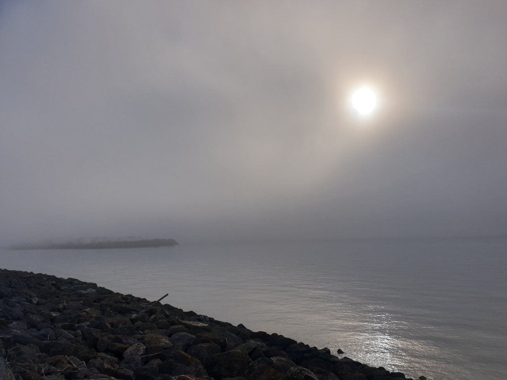 The sun glowing through thick grey cloud and mist over a calm sea
