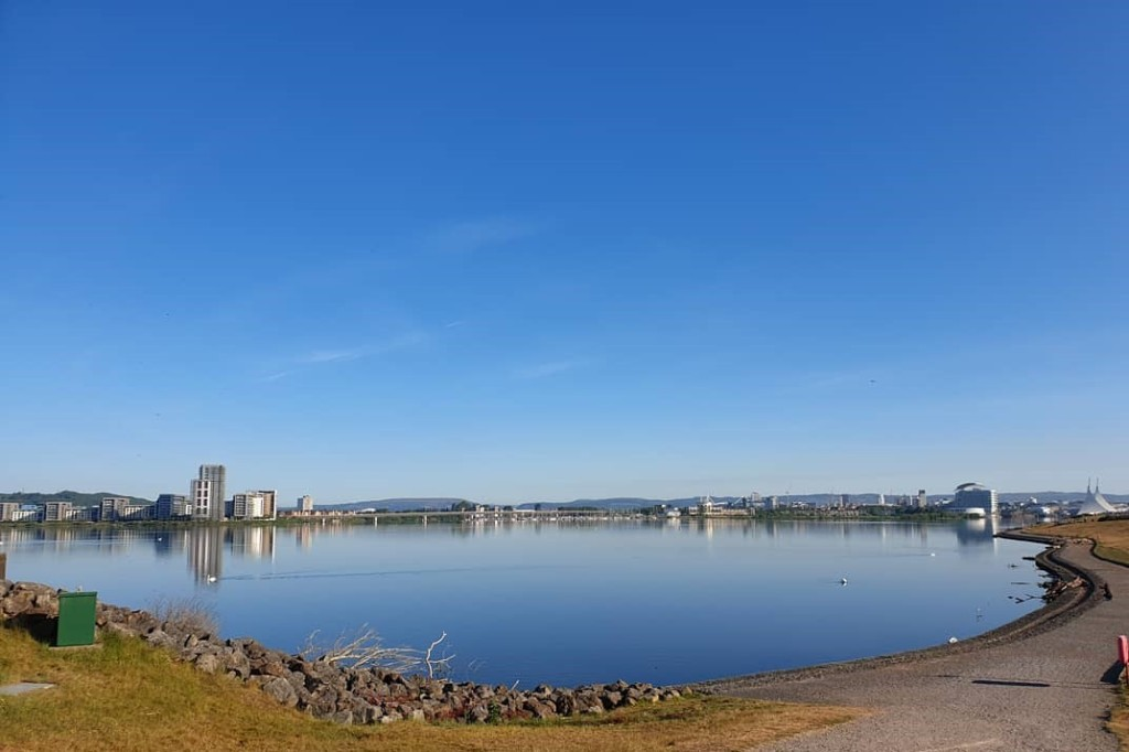 A view of Cardiff Bay lagoon looking back towards the city. It is a beautiful clear sunny day and the water is smooth and blue.