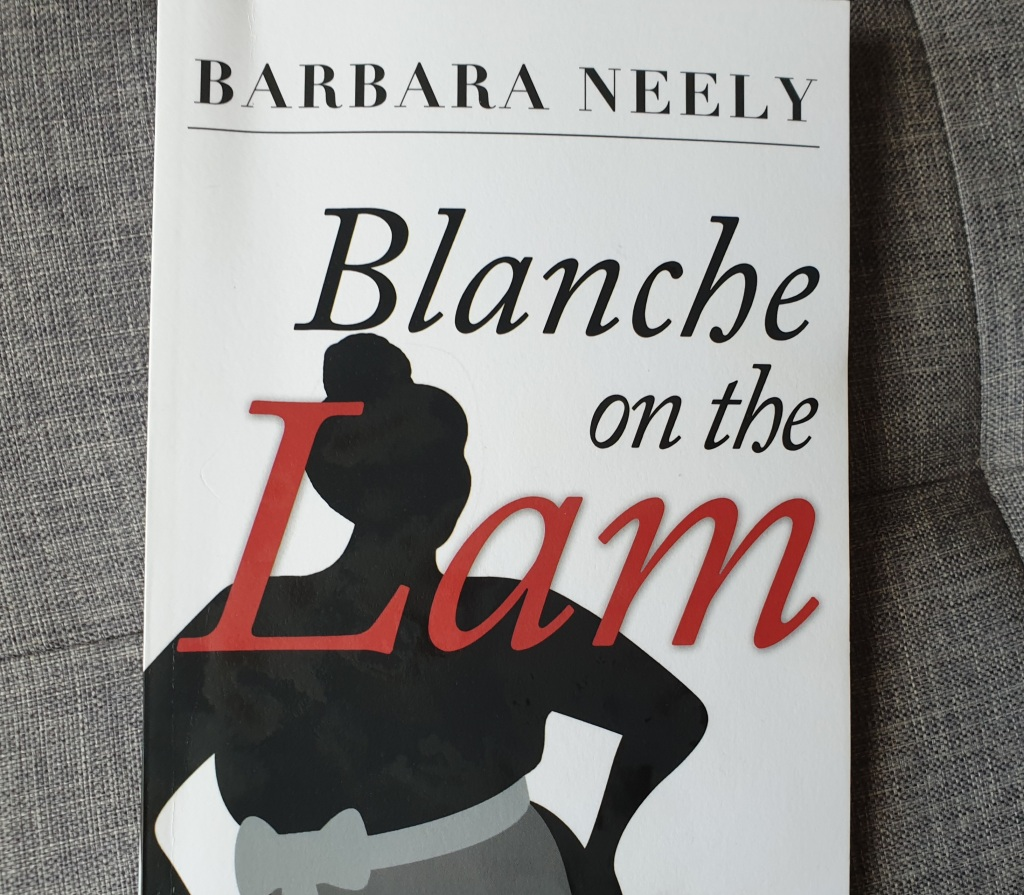 A copy of Blanche on the Lam by Barbara Neely. It is a plain white cover with the title a sillhouette of a plump black woman wearing an apron.