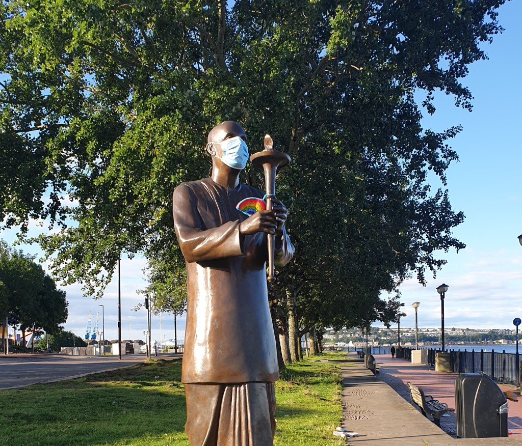 A statue of a monk holding a lamp. Someone has put a mask on his face and a knitted NHS rainbow in his hands.