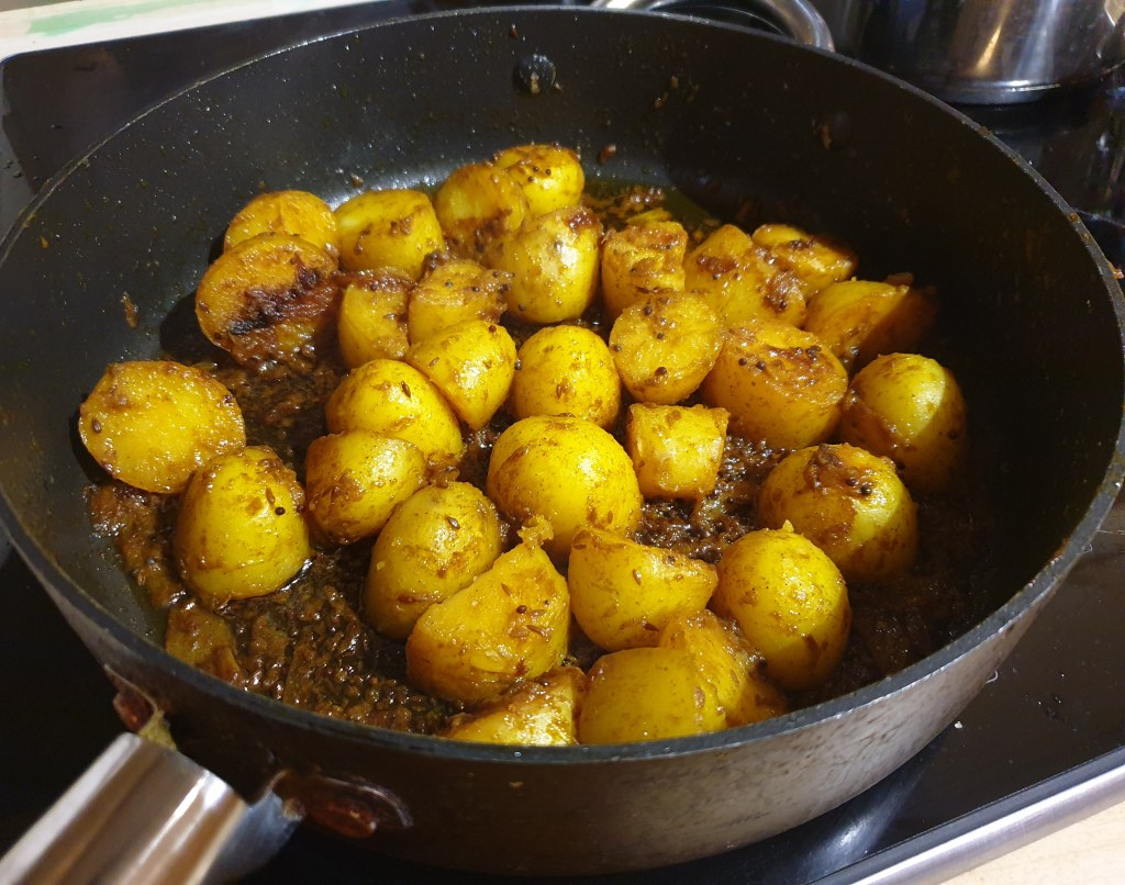 A large round saucepan containing a dry potato curry. The potatoes are golden with turmeric and flecked with fried onions.
