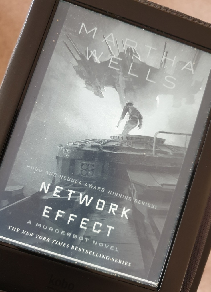 An ereader with the cover of Network Effect by Martha Wells. It shows Murderbot standing on top of a space ship.