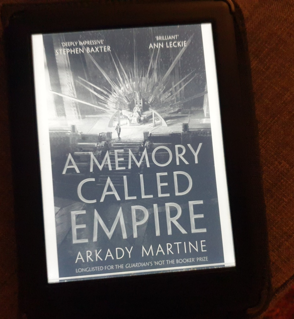 An ereader showing the cover of A Memory Called Empire. It shows a figure approaching an enormous spiked throne.