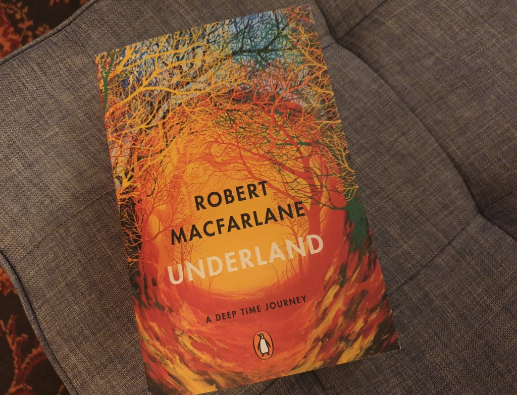 A copy of Underland by Robert Macfarlane. The cover is a painting of a path through woodland.