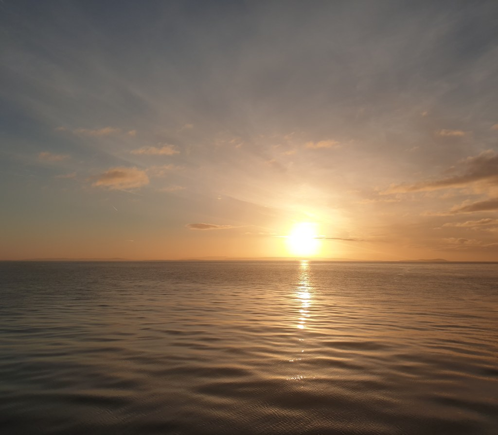 The sun rising over a calm sea on a clear morning