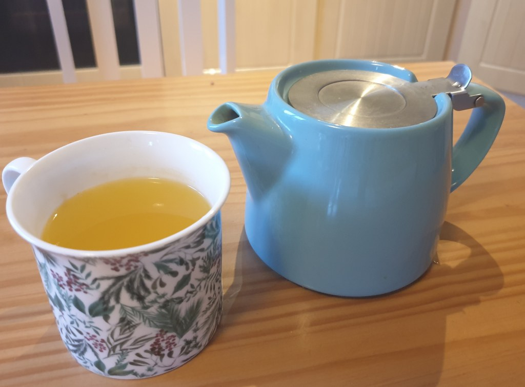 A flowery patterned mug full of bright yellow turmeric tea sitting in a table next to a light blue stump tea pot.