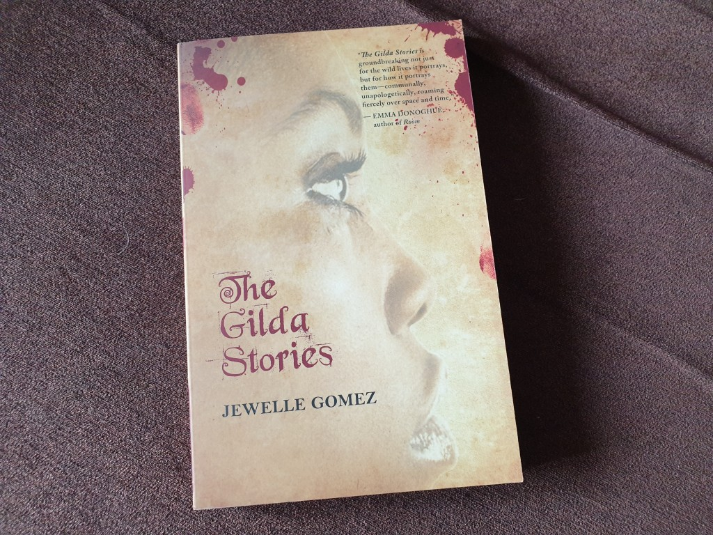 A copy of 'The Gilda Stories' by Jewelle Gomez. The cover shows a sepia-toned image of a black woman's face in prorile with drops of blood around the edges.